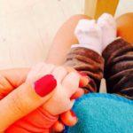 Meryem Uzerli holding her baby's hand